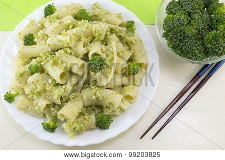 Pasta With Broccoli Served With Cooked Broccoli In A White Bow On A Wooden Table. Eating With Chopst