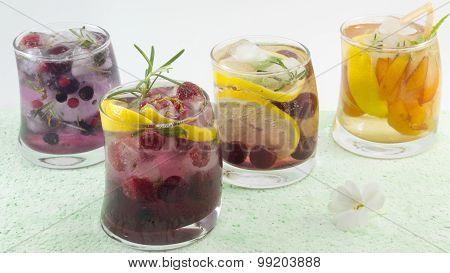 Natural Fruit Iced-t Juice With Ice, Lemon And Sliced Fruits In A Crooked Glass On Blue Table Backgr