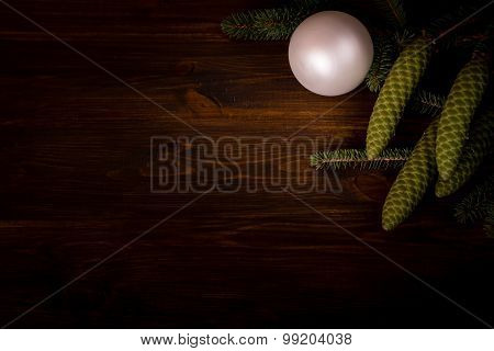 Spruce branch with cone and white ball on wooden planks