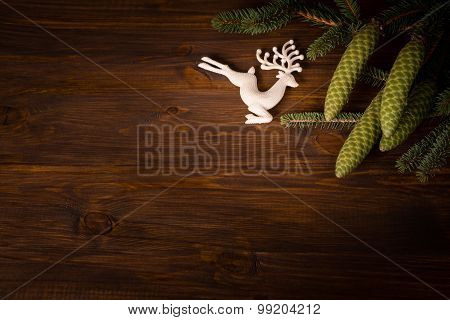 Spruce branch with cone and white deer on wooden planks