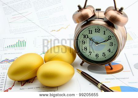 Three Golden Eggs With A Clock On Business And Financial Reports.