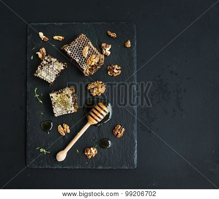 Honeycomb, walnuts and honey dipper on black slate tray over grunge dark backdrop, top view