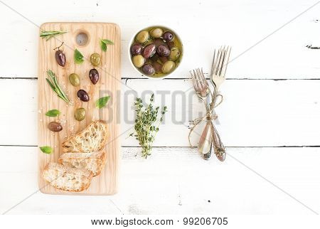 Mediterranean olives with herbs and ciabatta slices on rustic wooden board  over white background, t