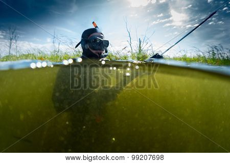 Man with spear gun preparing on the surface before spearfishing in the fresh water pond with poor visibility