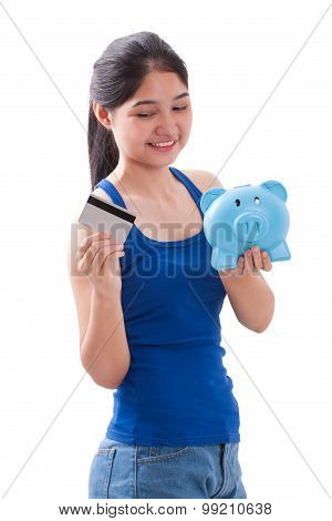 Young Woman holding piggy bank and card
