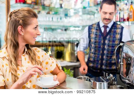 Girl in cafe stirring in cup while barista is preparing espresso and handling the bar