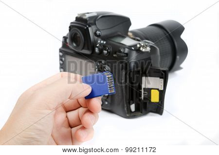 Hand holds SD Memory card - Flash card and DSLR camera on the background