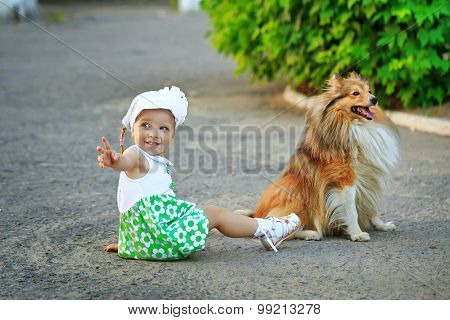 Little Girl And Dog Sitting On The Ground.