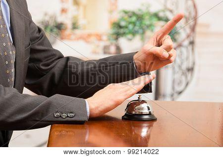 Customer Ringing Hotel Bell At Reception Desk