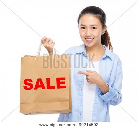 Asian woman finger point to shopping bag and showing a word sale