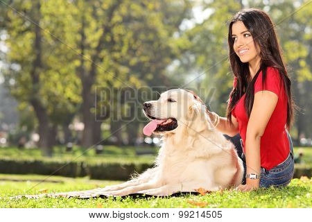 Beautiful girl sitting on the grass with her dog in a park