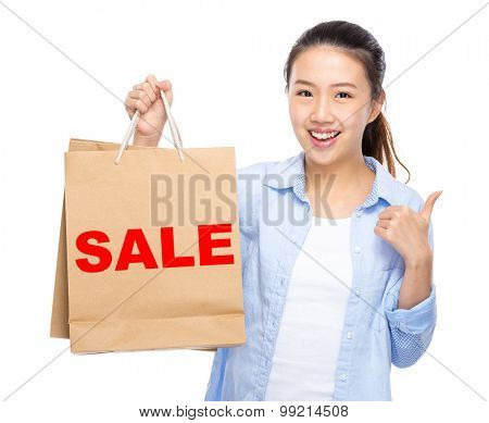 Woman with shopping bag and thumb up for showing a word sale