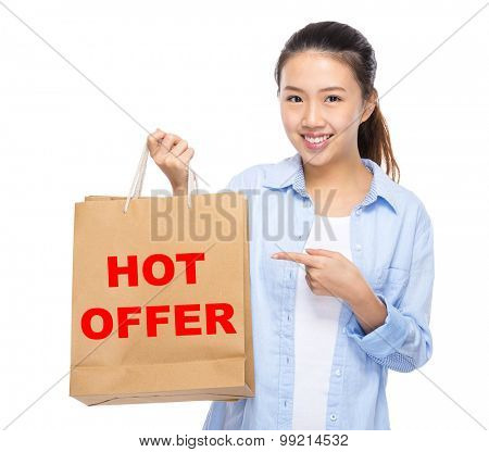 Asian woman finger point to shopping bag and showing hot offer