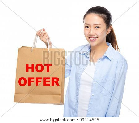 Young woman with shopping bag ans showing hot offer