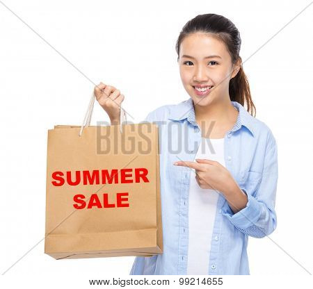 Asian woman finger point to shopping bag and showing summer sale