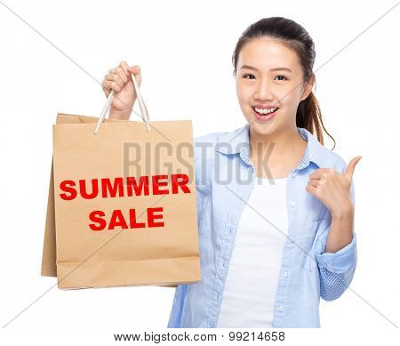 Woman with shopping bag and thumb up for showing summer sale