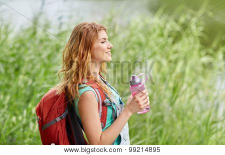 adventure, travel, tourism, hike and people concept - smiling young woman with backpack and bottle of water outdoors