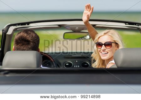 transport, road trip, leisure, gesture and people concept - happy man and woman driving in cabriolet car and waving hand
