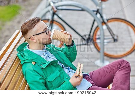 people, style, leisure and lifestyle - happy young hipster man drinking coffee cup and eating sandwich on city street