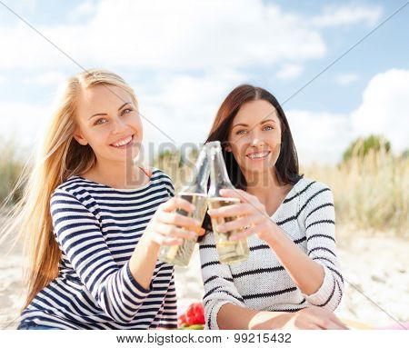 summer holidays, vacation, celebration and people concept - happy teenage girls or young women drinking beer or lemonade on beach