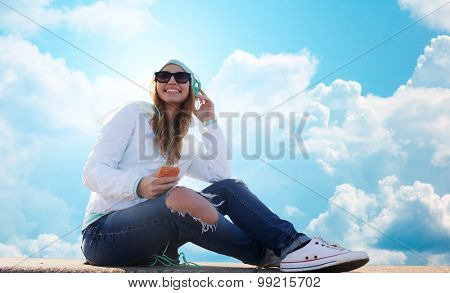 technology, lifestyle and people concept - smiling young woman or teenage girl with smartphone and headphones listening to music over blue sky and clouds background