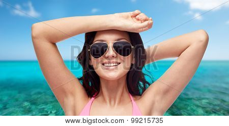 people, summer holidays, travel, tourism and beach concept - happy young woman in sunglasses and pink swimsuit over sea and blue sky background