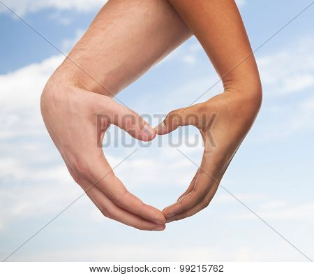 love and relationships concept - closeup of woman and man hands showing heart shape
