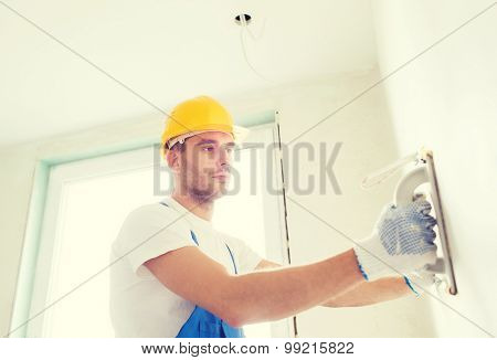 business, building, profession and people concept - builder with grinding tool indoors