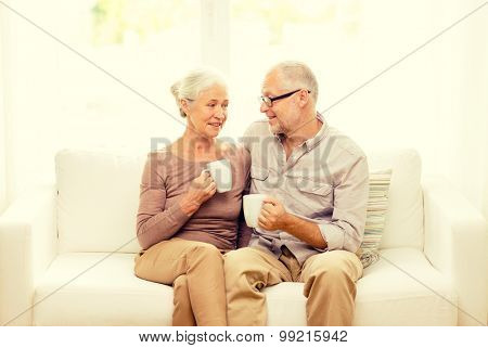 family, relations, age, drinks and people concept - happy senior couple with cups hugging on sofa at home