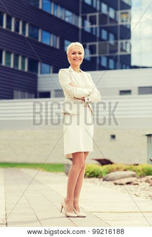 business, people and education concept - friendly young smiling businesswoman with crossed arms over office building