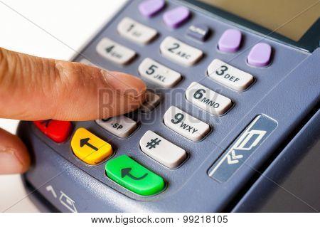 Man enters a PIN code on POS terminal