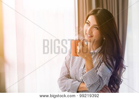 Asian Woman In Her Living Room Drinking Holding A Coffee Tea Mug With Sunrise Streaming In Through W