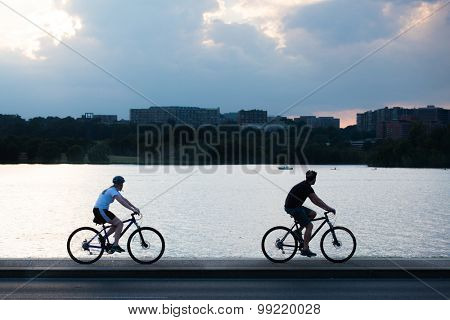 Two cyclist silhouette at bike way alongside the Potomac River in Washington DC, USA