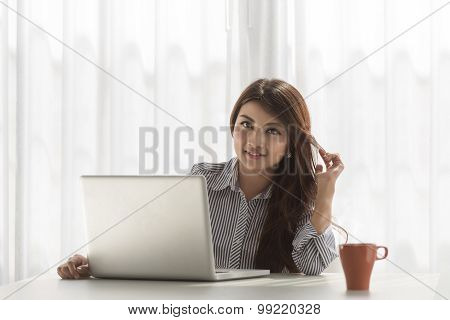 beautiful young asian woman working on her laptop in her home, look at the camera.