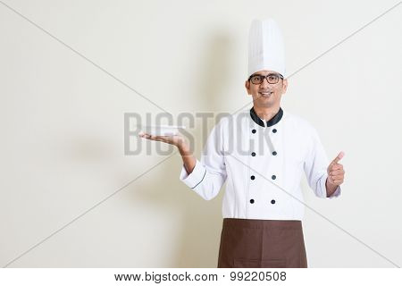 Portrait of handsome Indian male chef in uniform presenting an empty plate and thumb up, standing on plain background with shadow, copy space.