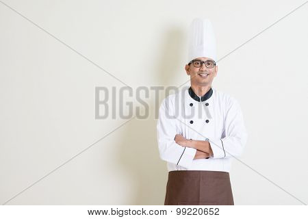 Portrait of handsome Indian male chef in uniform smiling, standing on plain background with shadow, copy space at side.