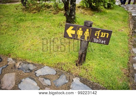 Wooden sign entrance to the toilet in Thai and English languages.