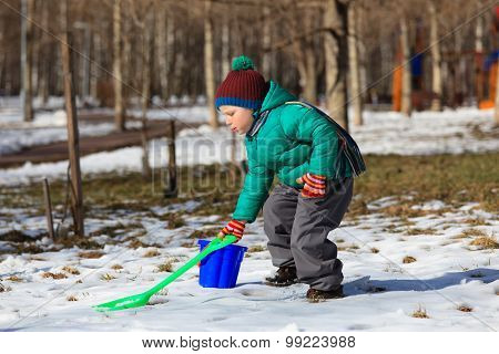 little boy digging in winter park
