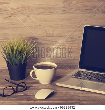 Wooden office table with laptop, cup of hot coffee, mouse, glasses and pot plant, in dramatic light vintage toned.