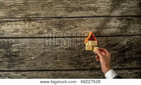 Businessman Assembling House Miniature On Table