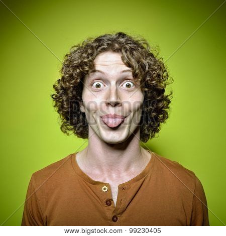 Young funny man shows his tongue, studio shot over green background. Lively face. Image toned and noise added.