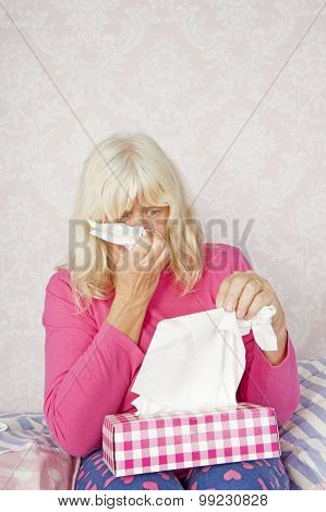 Woman On Bed Blowing Nose