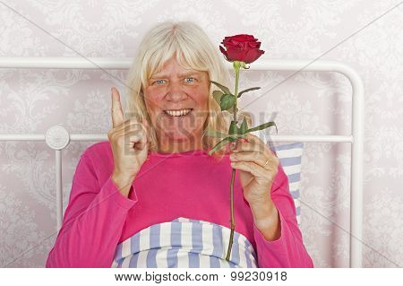 Cheerfull Woman In Bed With Rose
