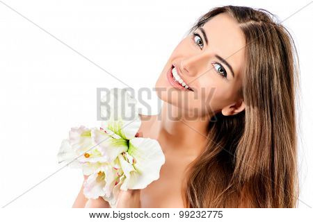 Beauty concept. Smiling young woman with clean fresh skin posing with tender flower. Skincare, bodycare. Spa. Isolated over white.
