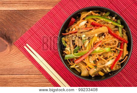 Asian salad with carrot, peppers and aubergines in the black bowl.