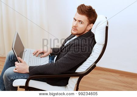 Happy young man using laptop sitting on armchair at home.