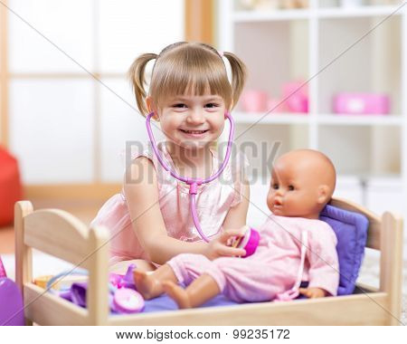 baby plays in doctor with toy doll and stethoscope