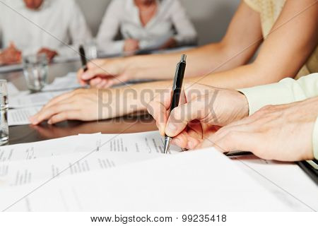 Hand signing contract in business meeting after negotiation