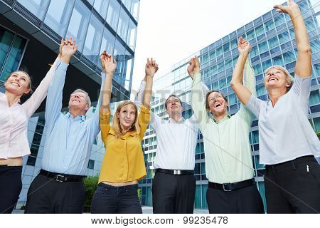 Happy business people lifting arms up together for motivation