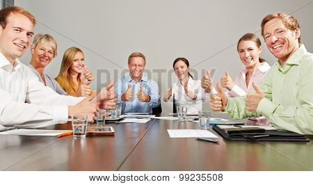 Many business people holding thumbs up together in a meeting